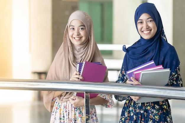 Moslim tiener houdt boeken vast