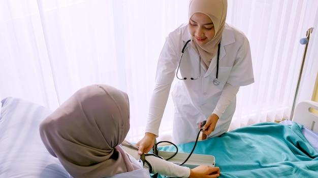 Moslim vrouwelijke arts die de bloeddruk van de patiënt controleert bij het ziekenhuisruimte.