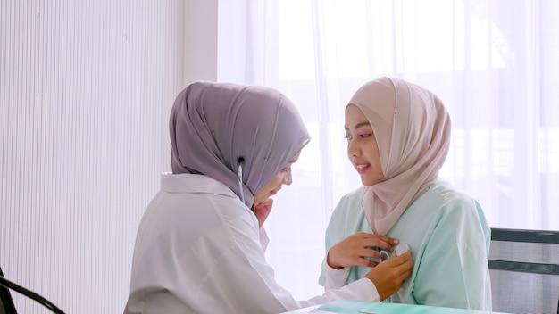 Moslim vrouwelijke arts die de gezondheid van de patiënt controleert bij het ziekenhuisruimte.