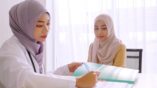Moslim vrouwelijke arts die het resultaat van het gezondheidsonderzoek van de patiënt opmerkt, geregistreerd in de ziekenhuiskamer.