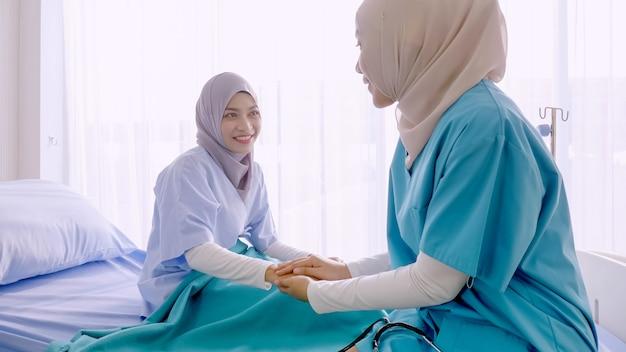 Moslim vrouwelijke arts die met patiënt bij het ziekenhuisruimte spreekt.
