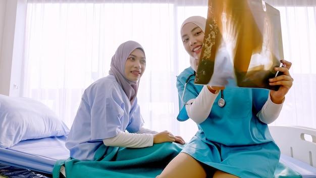 Moslim vrouwelijke arts die ziekte analyseren aan patiënt bij het ziekenhuisruimte.