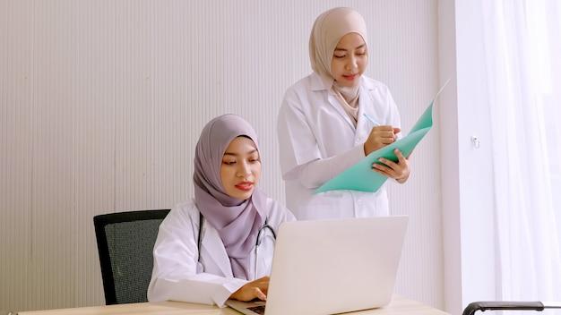 Moslim vrouwelijke arts en medische assistenten samen te werken in het ziekenhuis kamer.