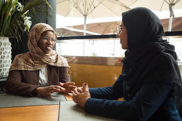 Moslim vrouwelijke collega's chatten tijdens de lunchpauze