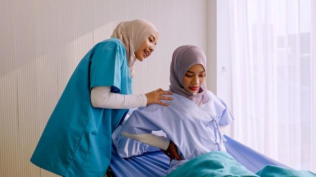 Moslim vrouwelijke fysiotherapeut die patiënt behandelen bij het ziekenhuisruimte.