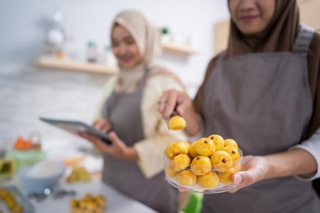 Moslim vrouwelijke hand die haar nastar-snackproduct inpakt