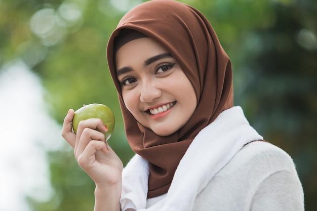 Moslim vrouwelijke sport die een appel eet