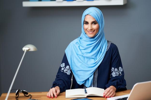 Moslim vrouwelijke student leren in bibliotheek