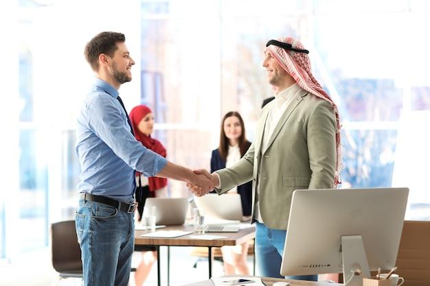 Moslim zakenman handen schudden met collega in kantoor