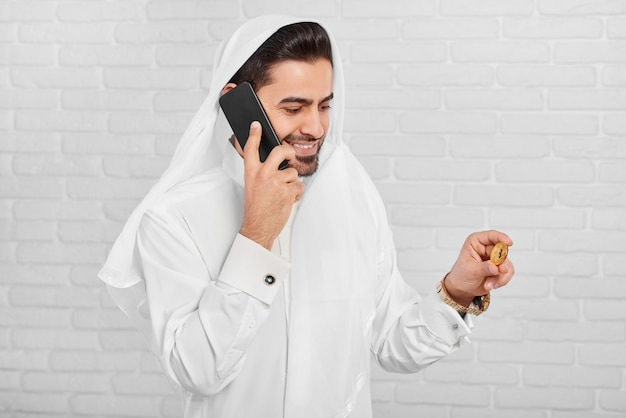 Moslim zakenman in traditionele slijtage houdt bitcoin en praat aan de telefoon