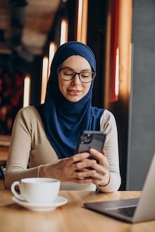 Moslim zakenvrouw die op de computer in een café werkt