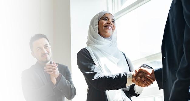 Moslim zakenvrouw handen schudden voor een zakelijke overeenkomst
