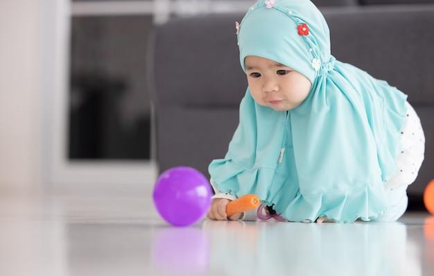 Moslimbaby speelt met kleurrijk speelgoed in de woonkamer.