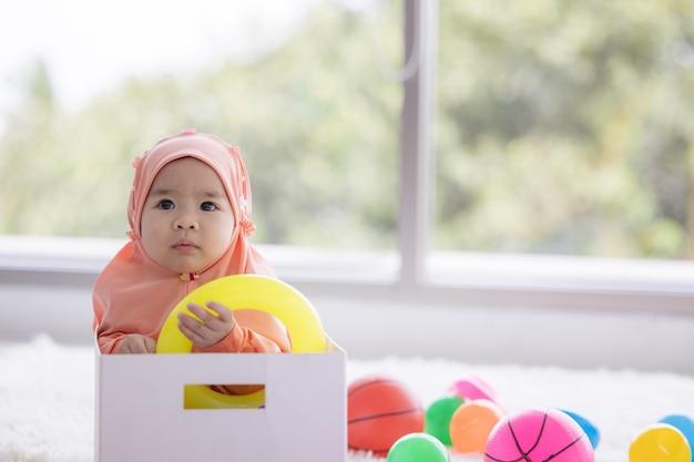 Moslimbaby speelt met kleurrijk speelgoed in de woonkamer