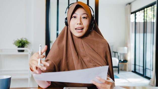 Moslimdame draagt een koptelefoon met behulp van een computerlaptop praat met collega's over een verkooprapport in een videogesprek terwijl ze op afstand vanuit huis in de woonkamer werkt.