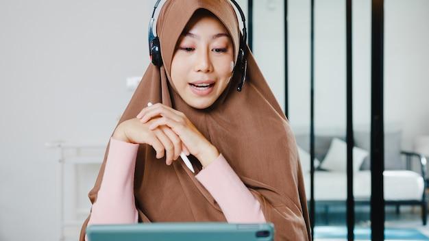 Moslimdame draagt een koptelefoon met behulp van een digitale tablet praat met collega's over het verkooprapport in een videoconferentiegesprek terwijl ze vanuit huis in de keuken werkt.