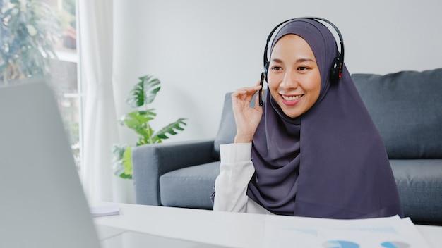 Moslimdame draagt een koptelefoon met behulp van een laptop praat met collega's over het plan in een videoconferentiegesprek terwijl ze vanuit huis in de woonkamer werkt.