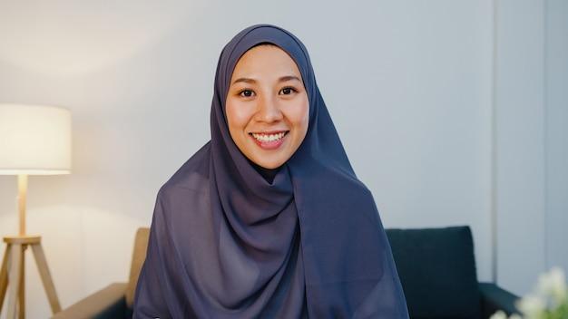 Moslimdame draagt hijab met behulp van computerlaptop praat met collega over plan in videogesprekvergadering terwijl ze op afstand werkt vanuit huis 's nachts in de woonkamer.