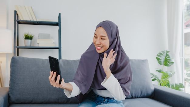 Moslimdame draagt hijab met behulp van een videogesprek met een stel thuis.