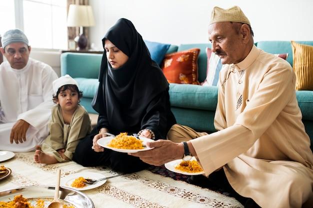 Moslimfamilie die diner op de vloer hebben