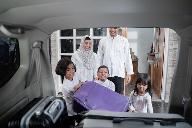 Moslimfamilie die koffers in de auto plaatst