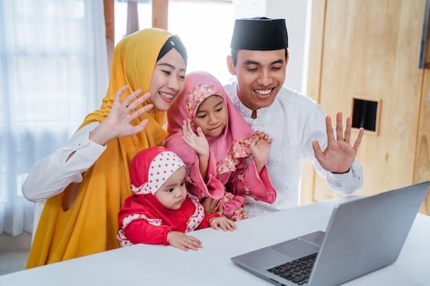 Moslimfamilie die laptop met behulp van om vrienden te bellen tijdens quarantaine op eid mubarak-viering