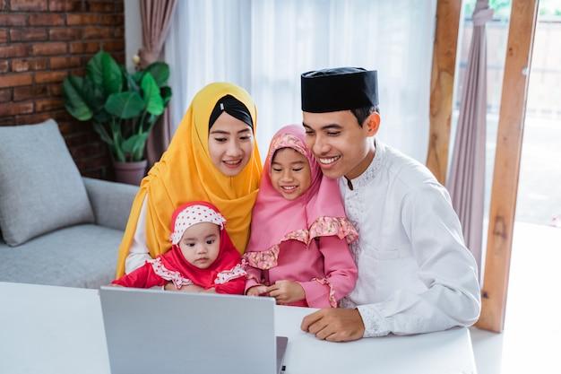 Moslimfamilie die laptop met behulp van om vrienden te bellen
