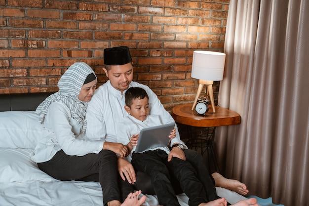 Moslimfamilie die tablet op het bed gebruiken