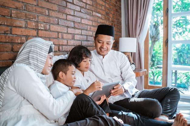 Moslimfamilie die tablet togethe gebruiken