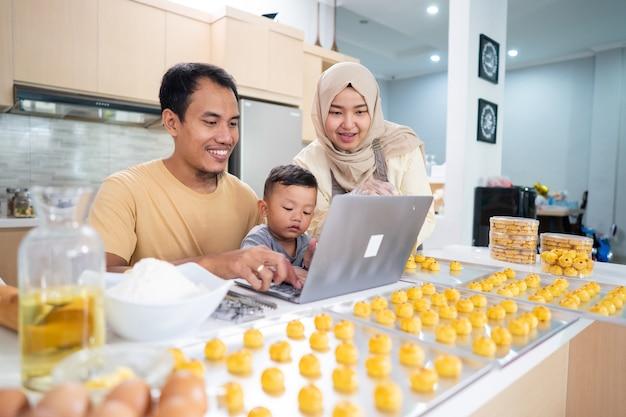 Moslimfamilie die thuis samen nastar-taart kookt. vader met behulp van laptop