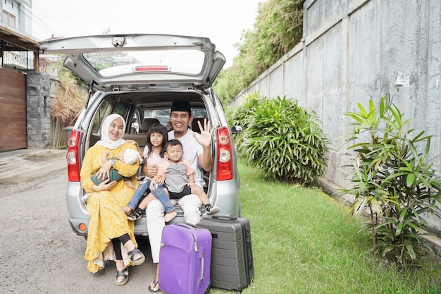 Moslimfamilie klaar om op vakantie te gaan terwijl ze samen op de kofferbak van hun auto zitten