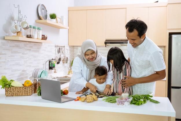 Moslimgezin met twee kinderen die samen thuis koken en zich voorbereiden op het diner en vasten tijdens de iftarpauze break