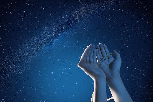 Moslimhanden die met gebedparels bidden bij openlucht