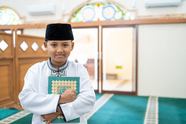 Moslimjongen die heilige koran houdt