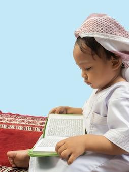 Moslimjongen in een jurk die de koran leest