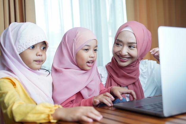 Moslimkinderen met hijabs kijken naar online lessen op een laptop