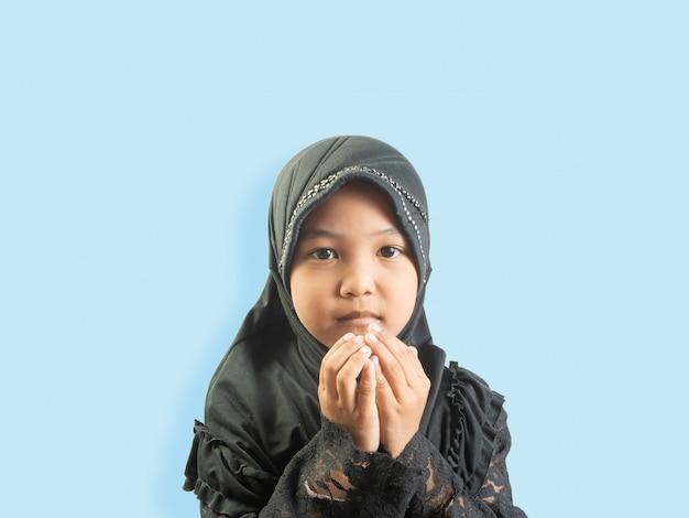 Moslimmeisje in een jurk op zoek naar zegeningen voor god