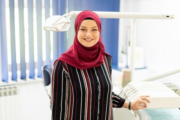 Moslimmeisje uit het midden-oosten binnen het kantoor van de tandarts