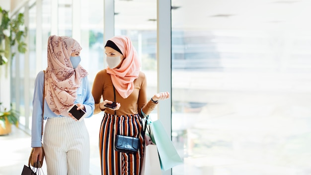 Moslimmeisjes die met gezichtsmaskers in het winkelcentrum rondhangen