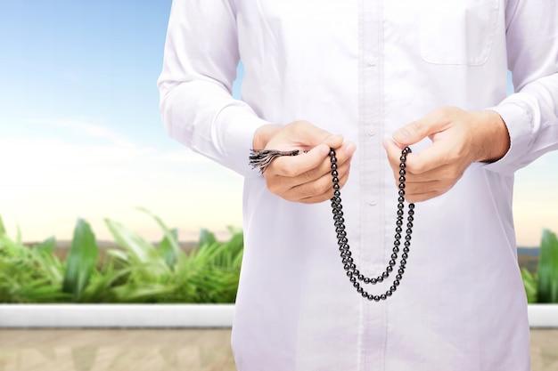 Moslimmens die met gebedparels bidden op zijn handen