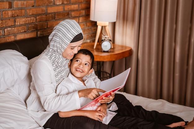 Moslimmoeder die een boek met haar zoon leest