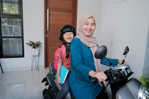 Moslimmoeder die haar dochter 's ochtends op de motor naar school brengt. aziatische basisschoolleerling terug naar school