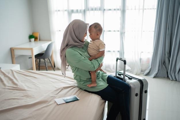Moslimmoeder draagt haar baby zittend op het bed