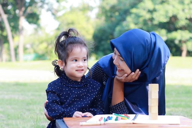 Moslimmoeder en dochter genieten van ontspannen in het park.