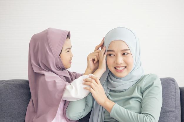 Moslimmoeder in hijab is haar dochtertje dat in de woonkamer zit. liefdevolle relatie