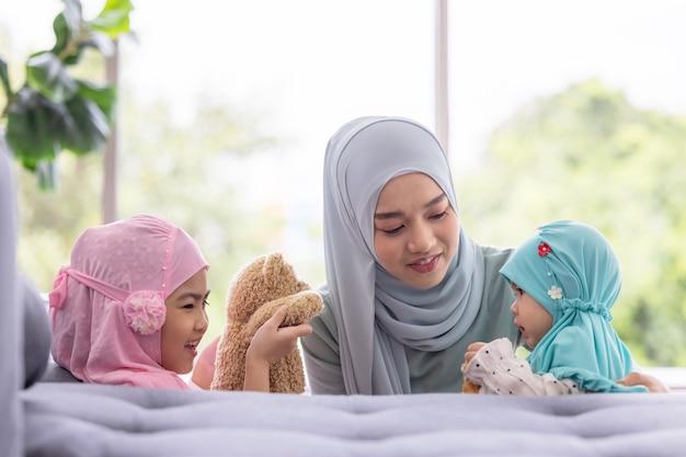 Moslimmoeder in hijab is haar dochtertje in de woonkamer, liefdevolle relatie