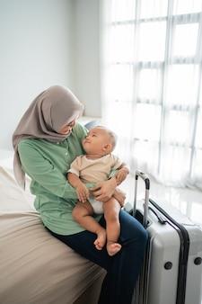 Moslimmoeders dragen hun baby's zittend op het bed