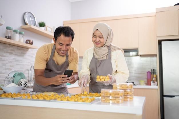 Moslimpaar gebruikt mobiele telefoon om hun snackproduct voor eid mubarak . te promoten