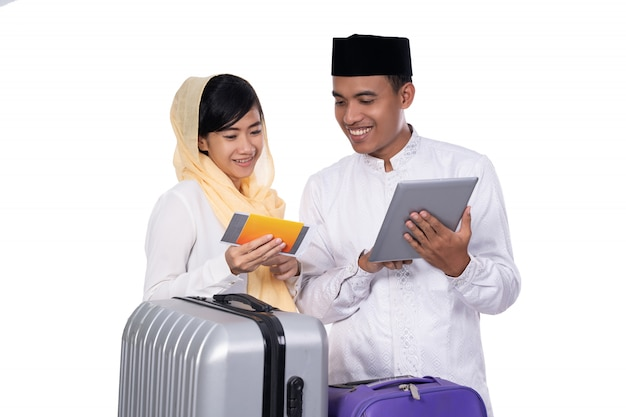 Moslimpaar met koffer die tablet samen gebruiken