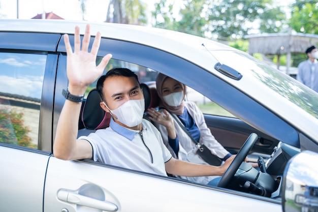Moslimpaar met maskers die vanuit de auto naar de camera zwaaien